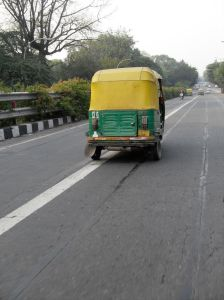A tuk-tuk on a very quiet roadway in Delhi.